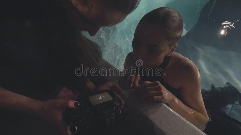 Da mulher do fotógrafo modelo de forma junto que olha a foto após a sessão subaquática na piscina foto de stock