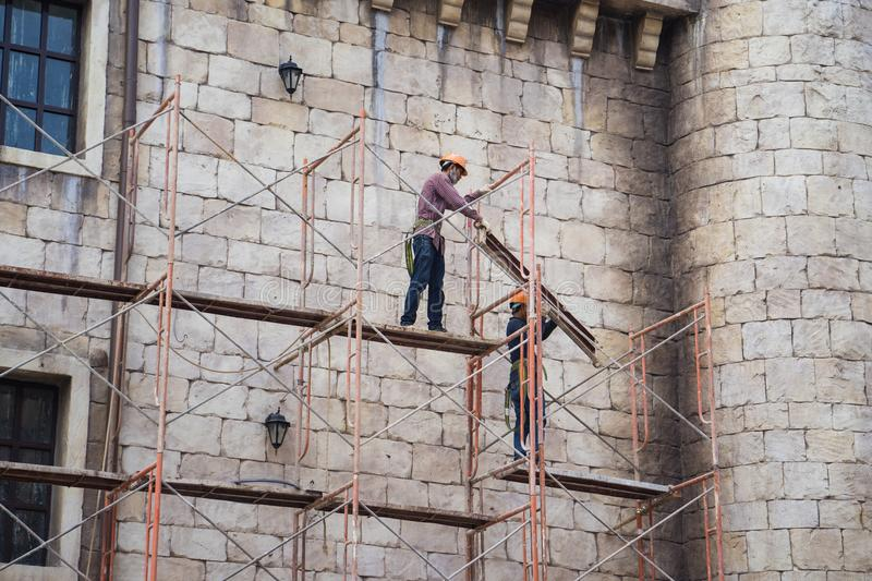Da Nang, Vietnam - Apr 2, 2016: Workers with no protection belt fixed on scaffold at construction site in Hoa Vang district, Da Na. Ng province stock image