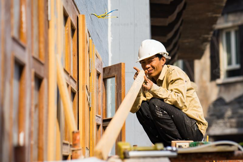 Da Nang, Vietnam - Mar 31, 2016: Carpenter checks the straight of wood plank before making window at Ba Na hills, Da Nang province stock photography