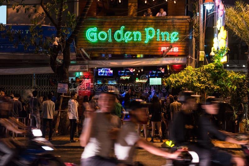 Night traffic in Danang, Vietnam. Da Nang, Vietnam - November 11, 2018: blurry night street traffic with a smiling woman on a bike in front of Golden Pine Pub stock photos