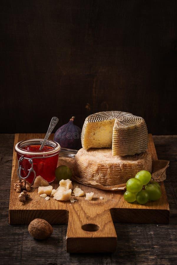 Da obscuridade vida ainda com placa, frutos e vinho do queijo fotografia de stock royalty free