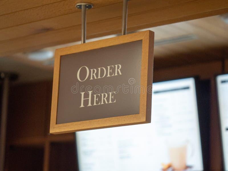 Da ordem sinal de madeira aqui que pendura no contador para viagem não ofuscante iluminado da ordem imagens de stock