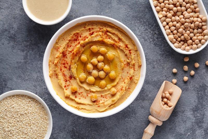 Da pasta árabe do Oriente Médio caseiro do mergulho de Hummus configuração lisa com paprika, tahini, sésamo, e azeite fotografia de stock