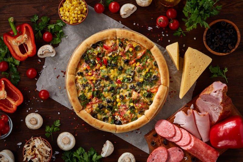 Da pizza vida ainda A pizza recentemente cozida e seus componentes arranjaram no fundo de madeira imagens de stock