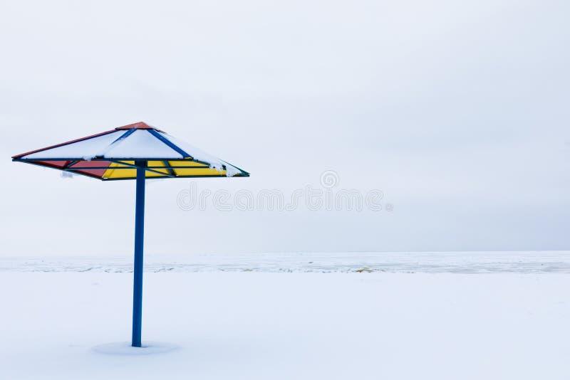Da solo il parasole o il parasole sulla spiaggia di inverno sotto la neve immagine stock libera da diritti