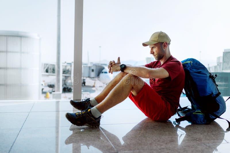 Da solo viaggiatore di viaggiatore con zaino e sacco a pelo che si siede sul pavimento del terminale di aeroporto e sull'imbarco  immagini stock libere da diritti