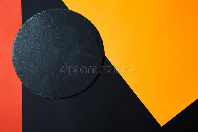 Da sopra del bordo nero vuoto del servizio dell'ardesia su fondo multicolore con composizione geometrica immagini stock libere da diritti