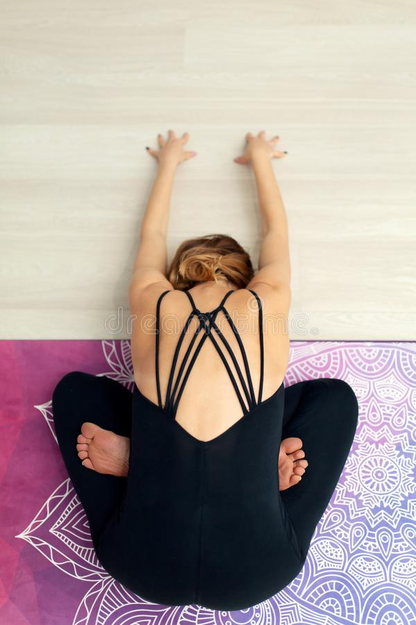 Da sopra yoga di pratica della giovane donna che allunga nella palestra Stile di vita di benessere e di misura immagini stock libere da diritti