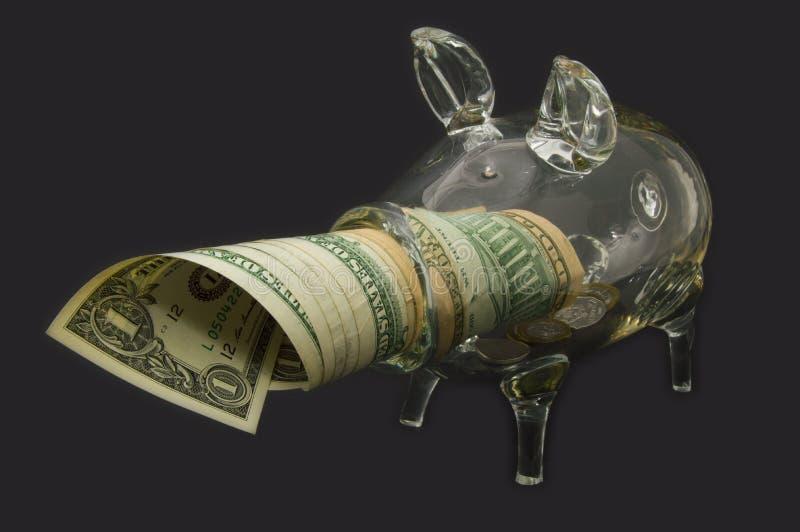 Da vista um mealheiro completamente com moedas do dinheiro C?dulas sob o mealheiro imagem de stock