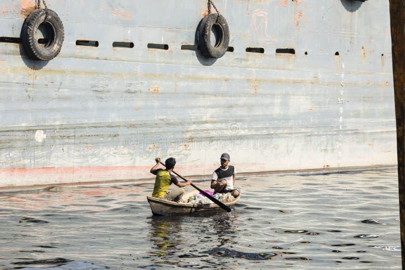 Dacca, Bangladesh, el 24 de febrero de 2017: Dos hombres montan su barco de madera entre las naves grandes en el río de Buriganga fotografía de archivo libre de regalías