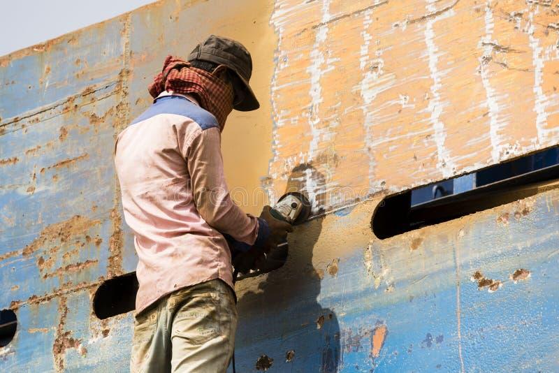 Dacca, Bangladesh, el 24 de febrero de 2017: Trabajador en un muelle de la nave en Dacca que muele una placa fotografía de archivo