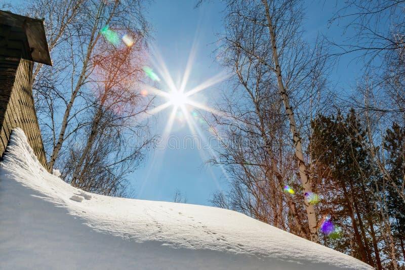 Dach des Landhäuschens mit dem Kamin bedeckt mit großer Schneeschicht Blauer Himmel mit Sonnenaufflackern auf Hintergrund Ländlic lizenzfreies stockfoto