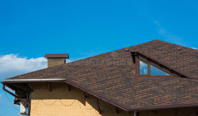 Dach mit Dachboden und Kamin unter klarem blauem Himmel stockbilder