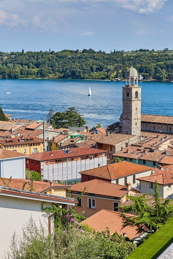 Dach mit roten Fliesenhäusern und Landschaft auf See Garda in Italien, mit Yacht lizenzfreies stockbild