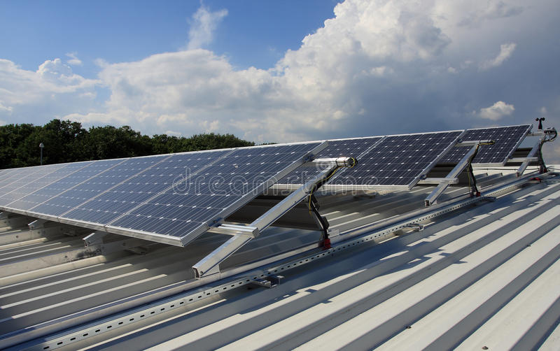 Dach mit Sonnenkollektoren. stockbilder