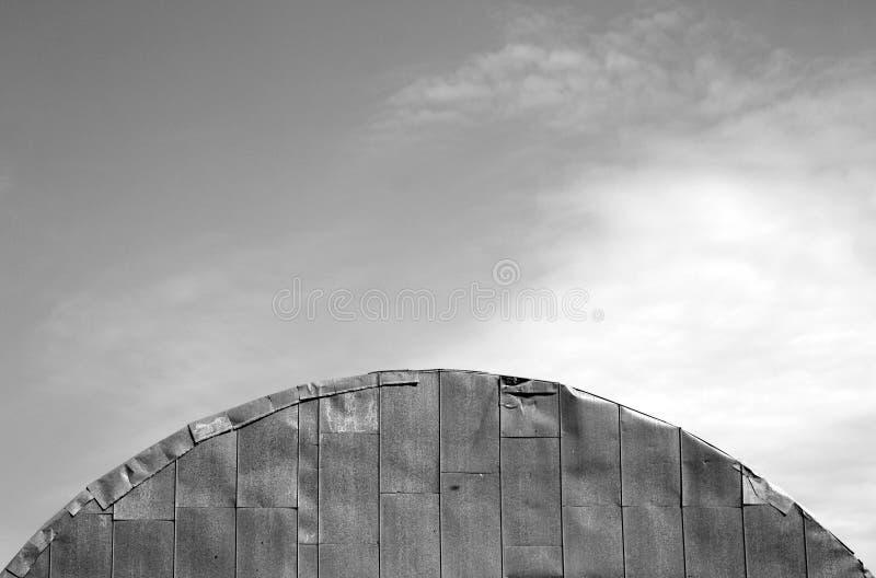 Dach stary metalu hangar przeciw chmurnemu niebu w czarny i biały zdjęcia royalty free