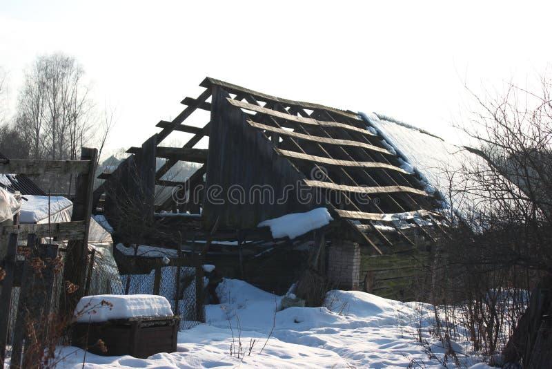 Dach stary zaniechany dom w wiosce w zimie Śnieżny i słoneczny dniu Opróżnia dom, bez ludzi łamających, niszczący, obrazy stock