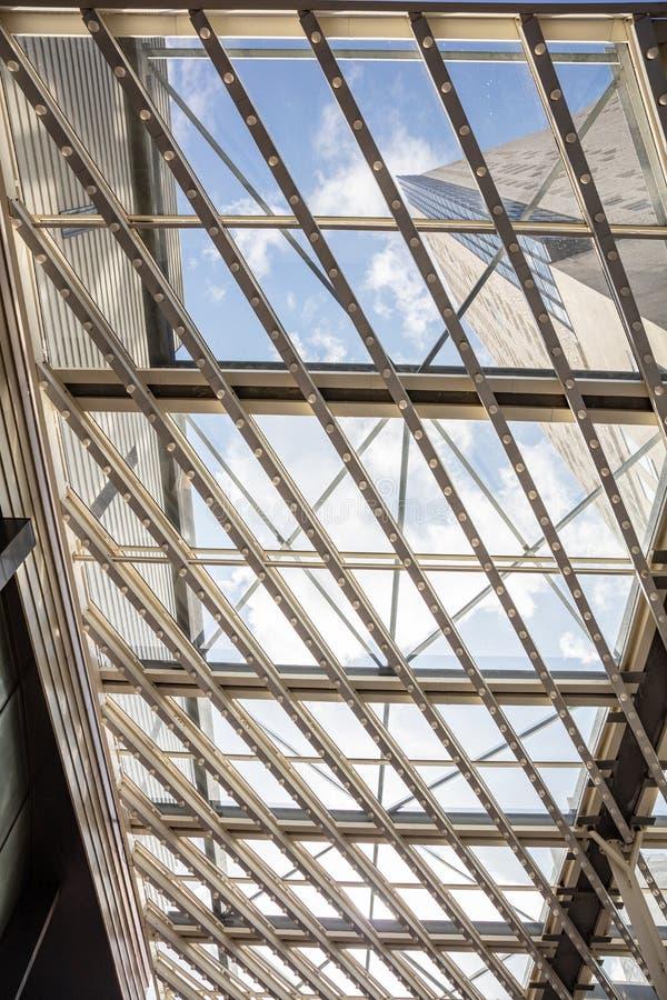 Dach szklany Niebieskie, mętne niebo przez metalową konstrukcję z szklanymi panelami, widokiem i naturalnym światłem obraz royalty free