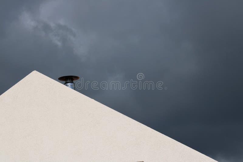 Dach z kominem w nieba chmurnym niebie obraz stock