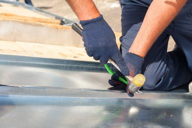 Dacharza budowniczego pracownik wykończeniowy składający metalu prześcieradło używać gumowego dobniaka zdjęcia stock