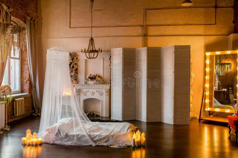 Dachboden-ähnlicher Raum mit einem Bett, eine Überdachung, ein weißer Kamin mit einer Blumenanordnung, ein weißer Schirm, ein gro lizenzfreie stockfotos