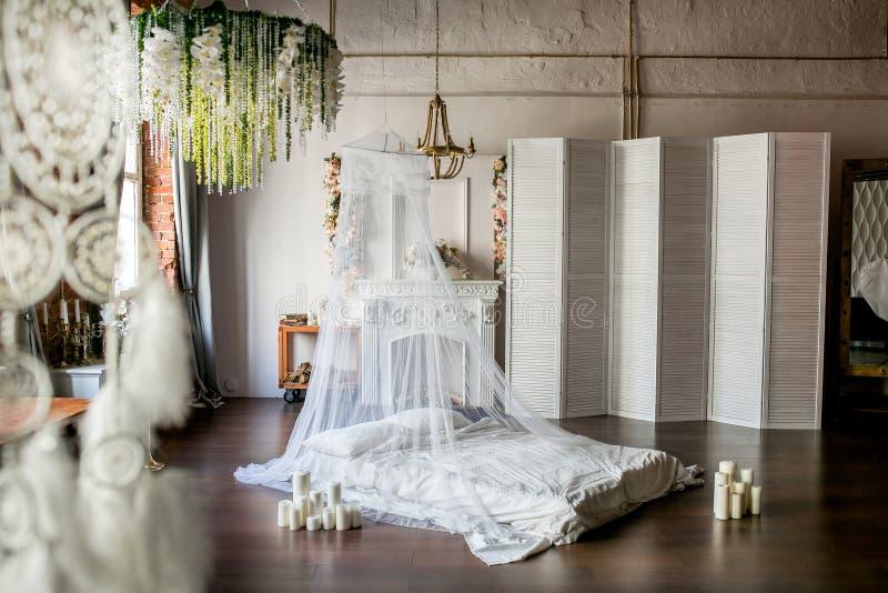 Dachboden-ähnlicher Raum mit einem Bett, einer Überdachung, einem weißen Kamin mit einer Blumenanordnung, einem weißen Schirm, ei lizenzfreie stockbilder