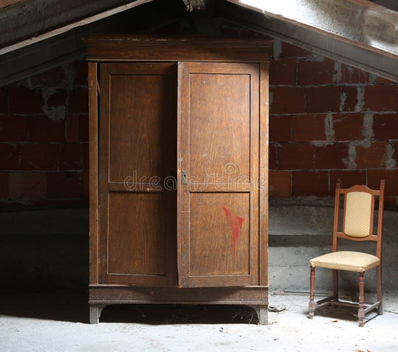Dachboden des Hauses mit einer hölzernen Garderobe und einem alten klapperigen Stuhl lizenzfreie stockfotografie