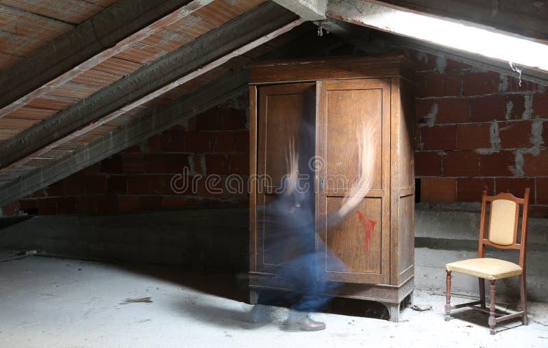 Dachboden mit einer alten hölzernen Garderobe und die Bewegung eines Geistes stockbilder