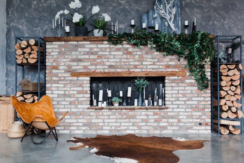 Dachbodenart Innenraum mit Ziegelsteinkamin, Kerzen, Grün, moderne Stuhlhaut von Kühen, graue Wand, firewoods, modernes Design lizenzfreie stockfotos