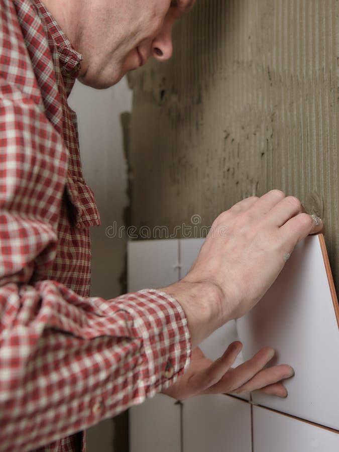 Dachdecker, der Keramikfliesen auf eine Wand installiert stockfotografie