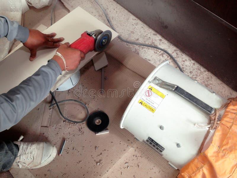 Dachdecker schnitt die Fliese durch Schleifmaschine und Staubkollektor stockbild