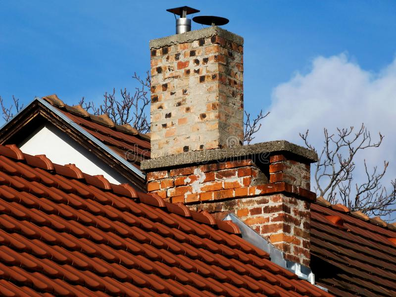 Dachdetail des roten Lehms mit Ziegelsteinkaminen unter blauem Himmel stockbilder