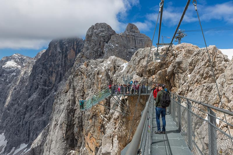 Austrian Dachstein Mountains with hikers passing a steel rope bridge royalty free stock images