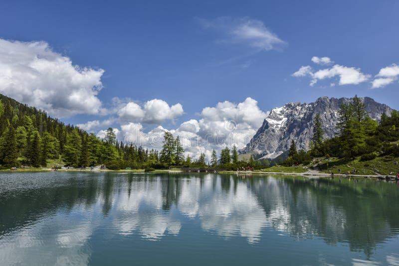 Dacht de hoogste berg Zugspitze van Duitsland ` s in de glasheldere wateren van het turkooise meer Seebensee, Oostenrijk na stock afbeelding