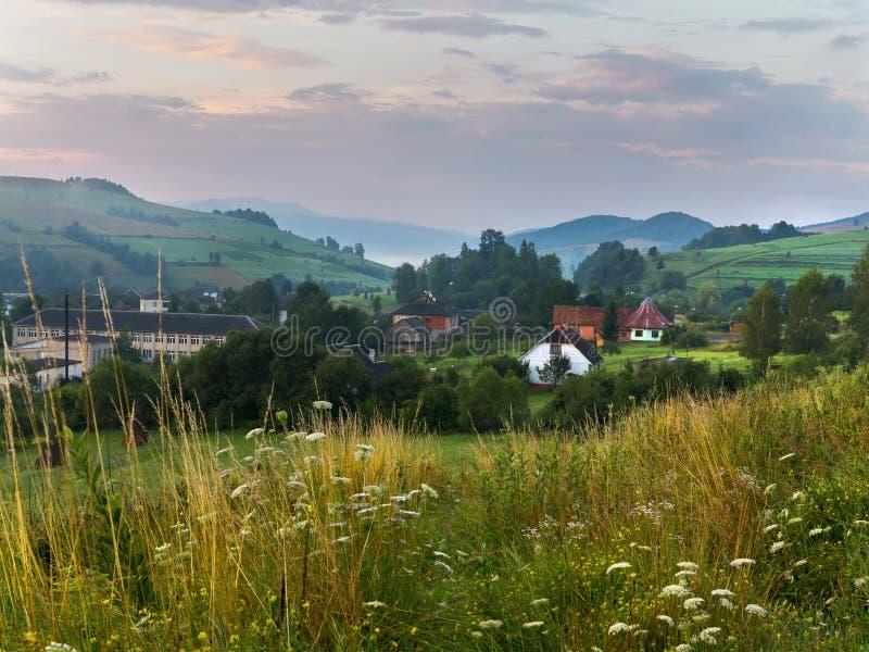 Dachy domy patrzeją out między zielonymi drzewami w dolinie zakrywającej z mgłą między wzgórzami zdjęcie royalty free