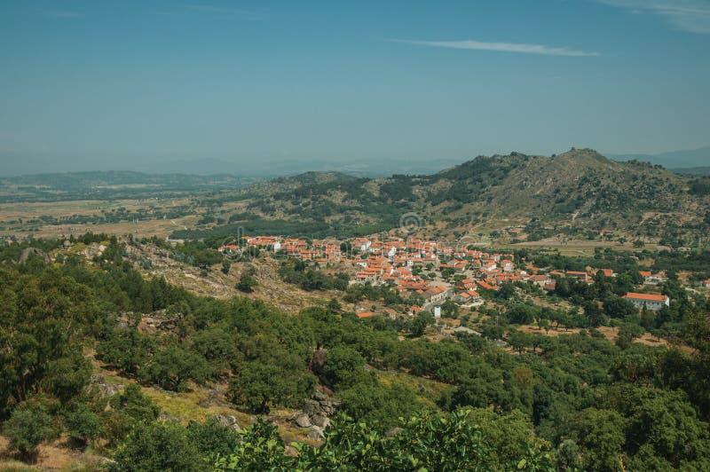 Dachy w górkowatym krajobrazie zakrywającym skałami i drzewem oliwnym blisko Monsanto fotografia royalty free