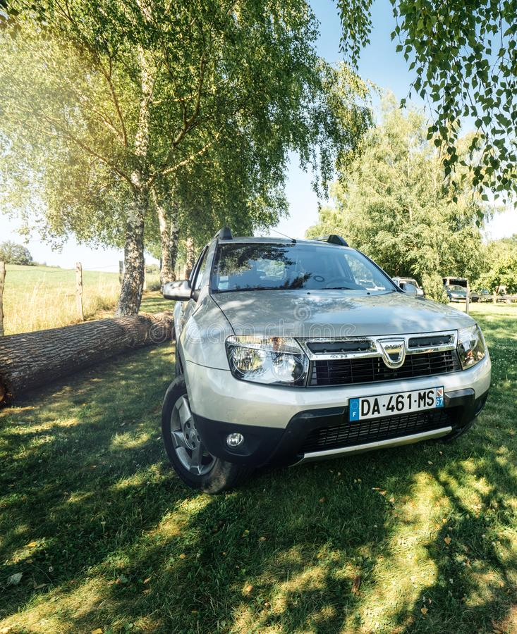Dacia Duster SUV in green fild French mountains under tree stock image