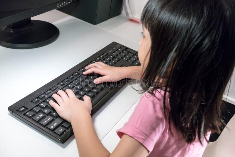 Dactylographie de pratique asiatique de clavier d'ordinateur de petite fille images libres de droits