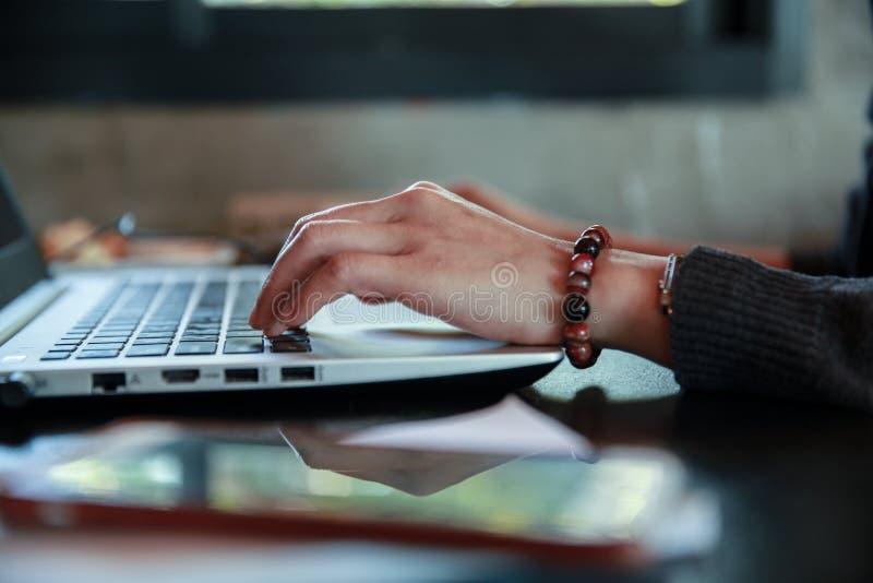 Dactylographie sur le clavier dans la vue de côté Travaillant sur l'ordinateur portable, avec le foyer en main dactylographiant s images stock