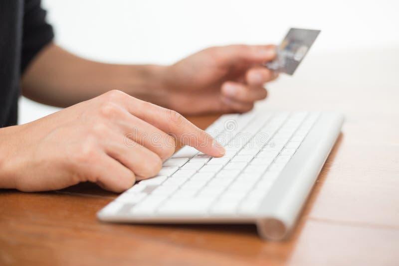 Dactylographie sur le clavier et tenir la carte de crédit photos stock