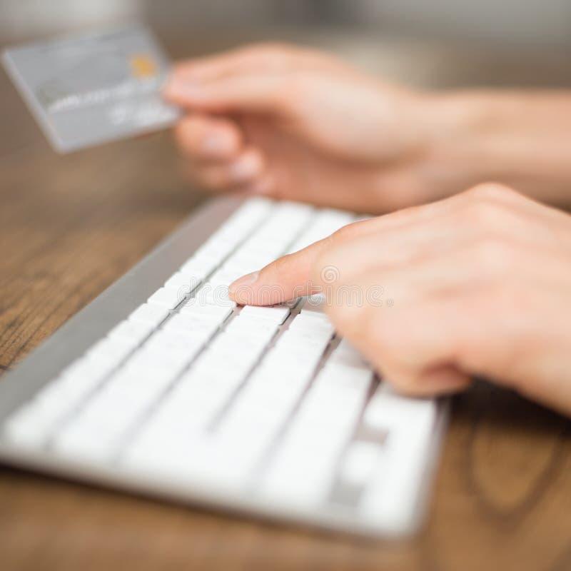Dactylographie sur le clavier et tenir la carte de crédit pour l'onl image libre de droits