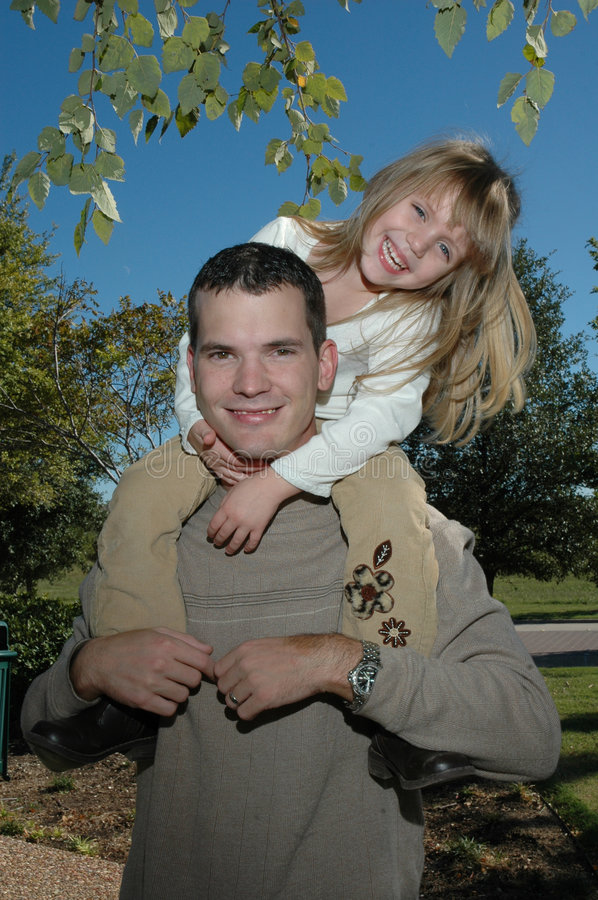 Dad. A father and child spend time at the park. Father giving his daughter a ride on his shoulders stock photos