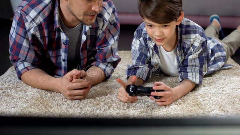Dad advising son how to operate video game joystick, support and care, leisure royalty free stock photography