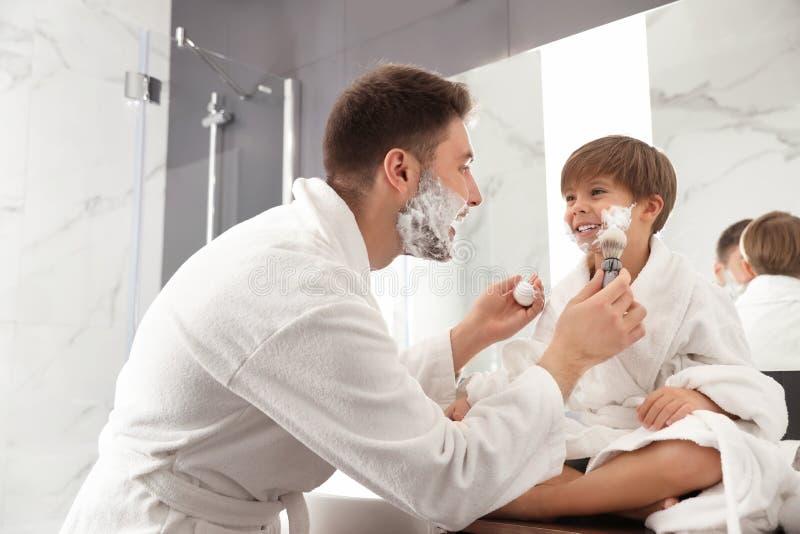 Dad applying shaving foam onto son`s face n bathroom stock photo