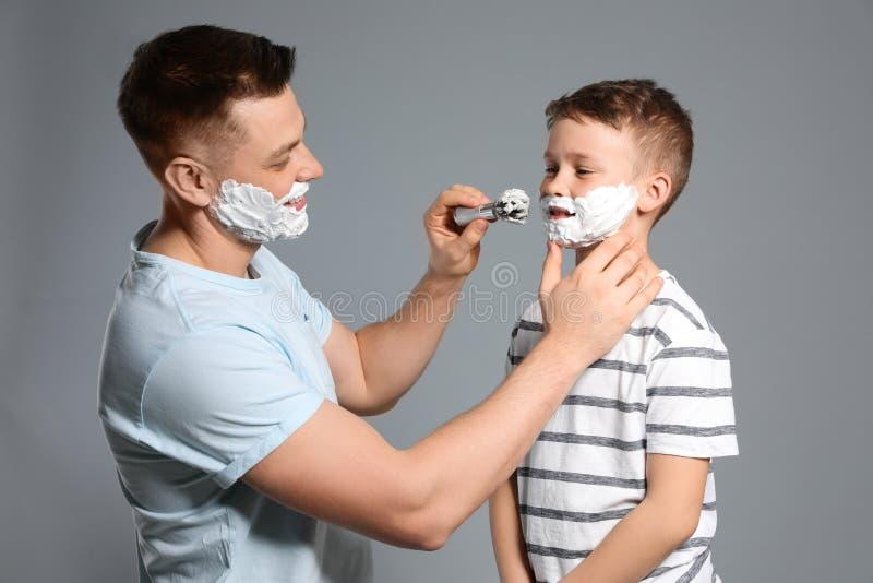 Dad applying shaving foam on son`s face, grey stock image