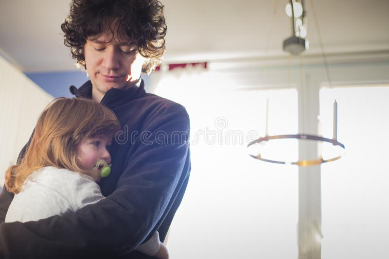 Dad and baby girl embracing at home stock photography