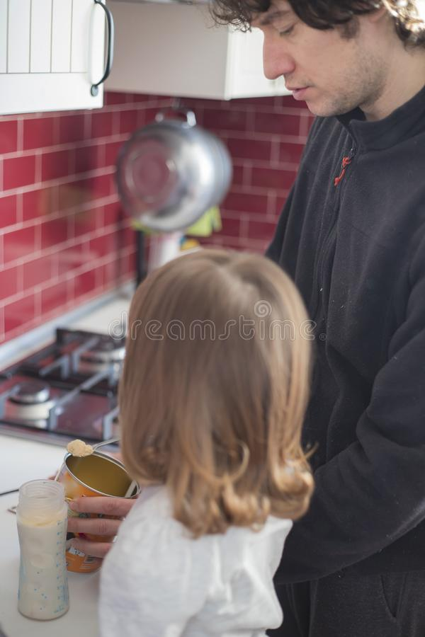 Dad and baby girl preparing breakfast stock image