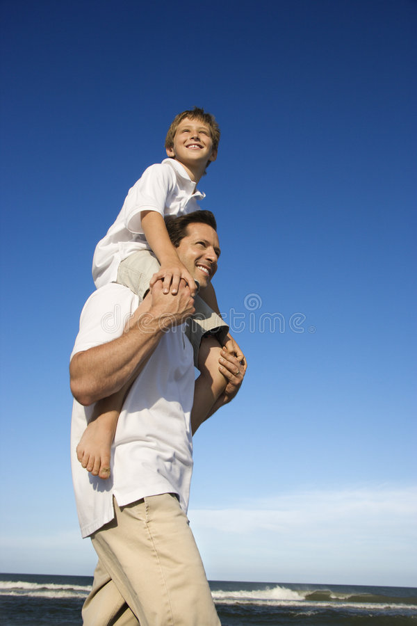 Dad carrying son. Caucasian father with pre-teen on shoulders on beach