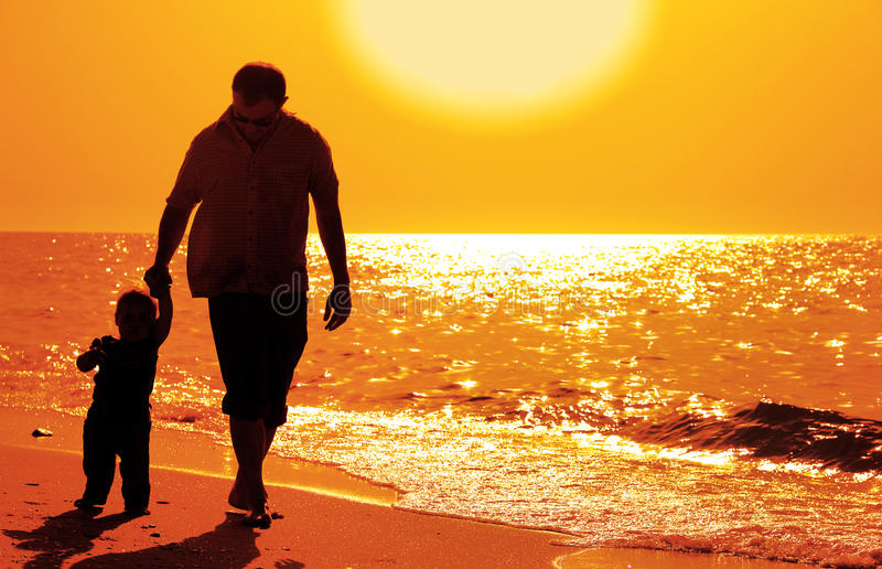 Dad and child on the beach. At at sunset