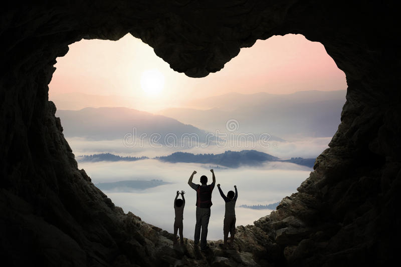 Dad and children inside cave shaped heart royalty free stock photos